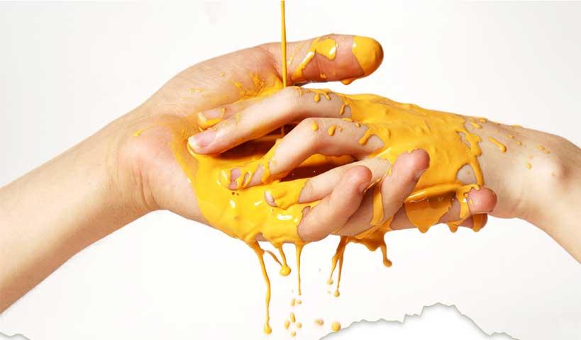 mani che si prendono e vernice gialla